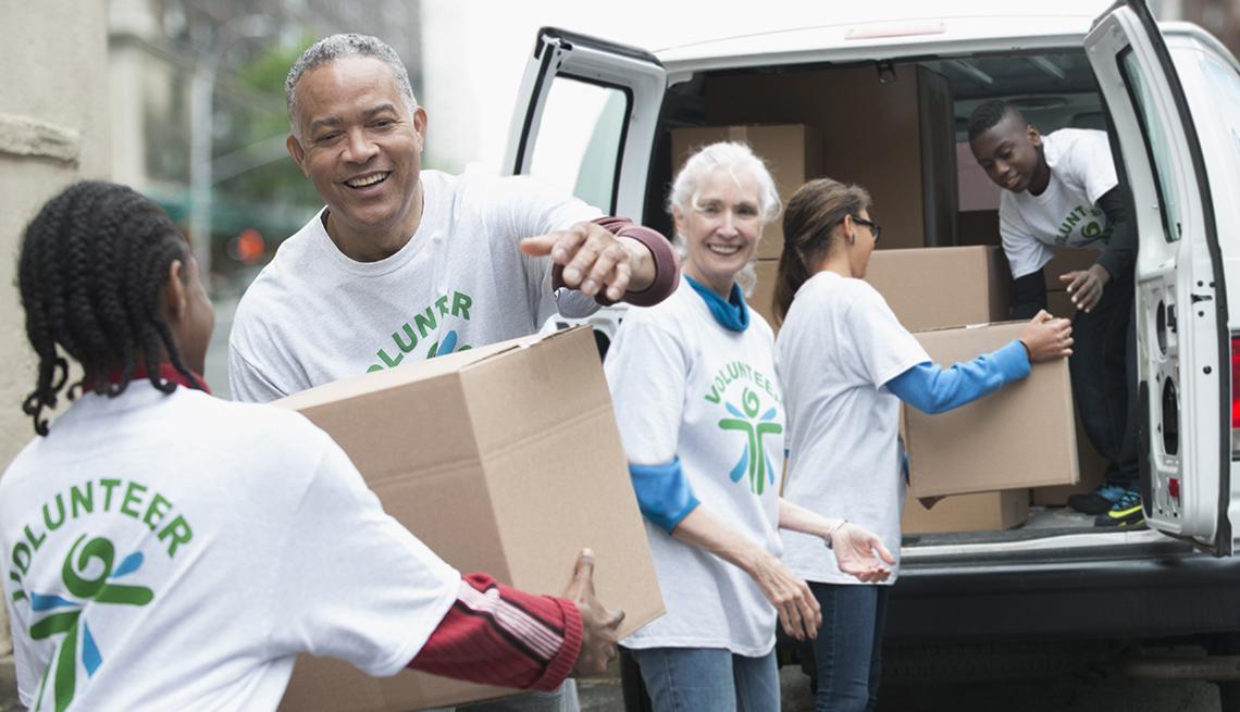 Grupo de voluntarios carga cajas en un vehículo