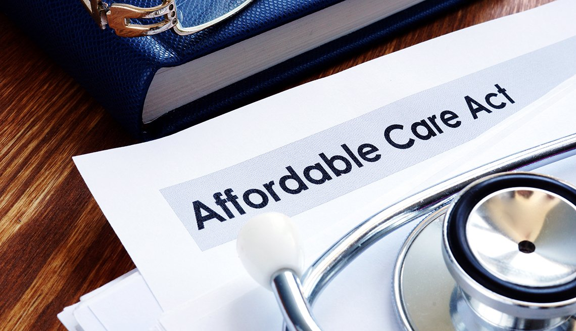 Affordable Care Act paperwork with a blue book and a stethoscope next to it