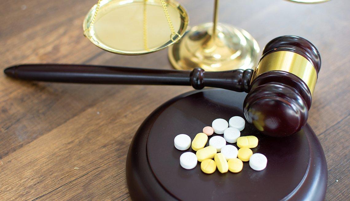 Un mazo de madera junto a una balanza de la justicia y algunas pastillas