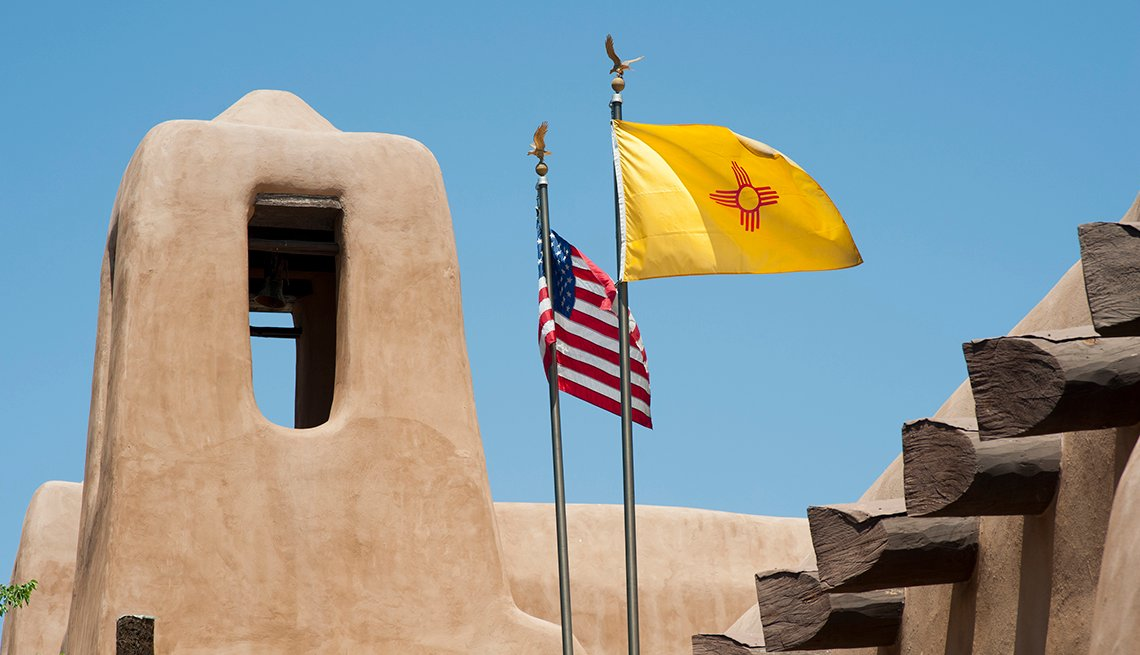 The flags of New Mexico and the United States fly over a building