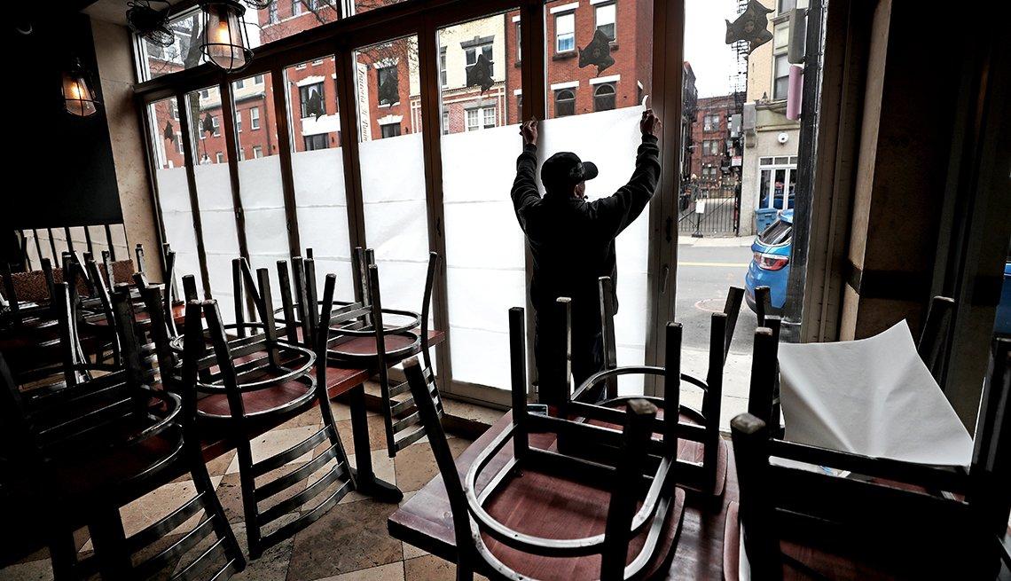 Un trabajador está poniendo papel sobre las ventanas de un restaurante cerrado