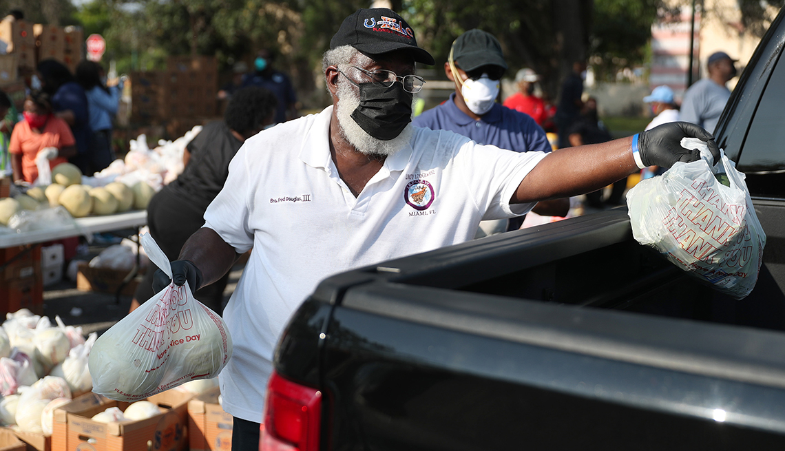 A volunteer places food in the back of a black truck