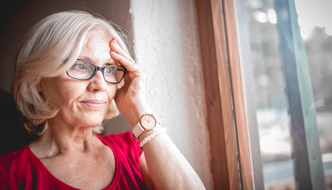 Mujer con gafas parece confundida cerca de la ventana