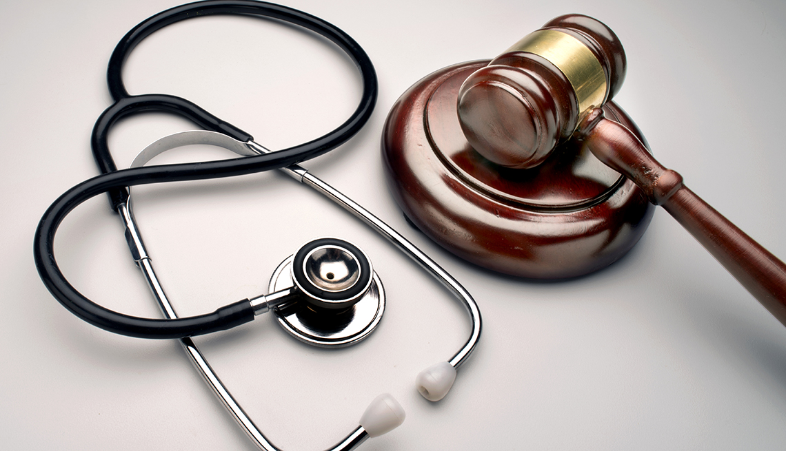 a brown wooden gavel next to a stethoscope