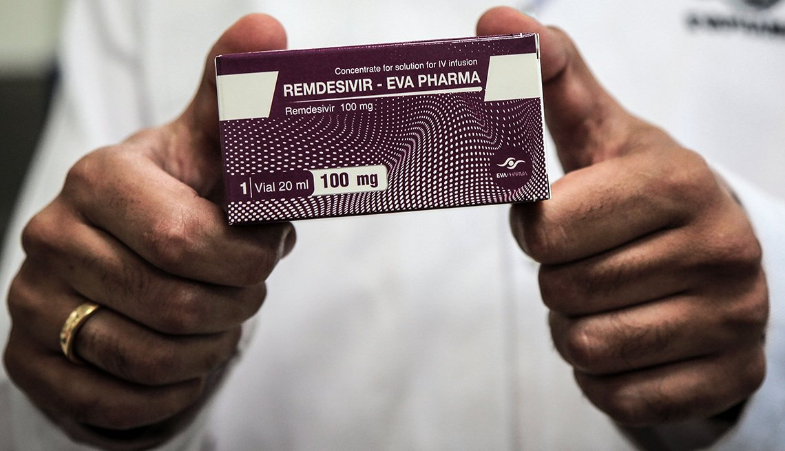 A person holding up a box of the drug Remdesivir