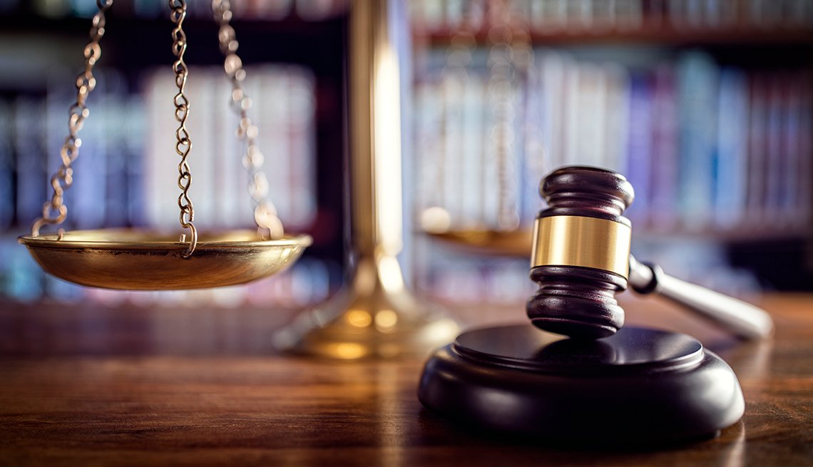 A brown gavel with the scales of justice sitting on a table