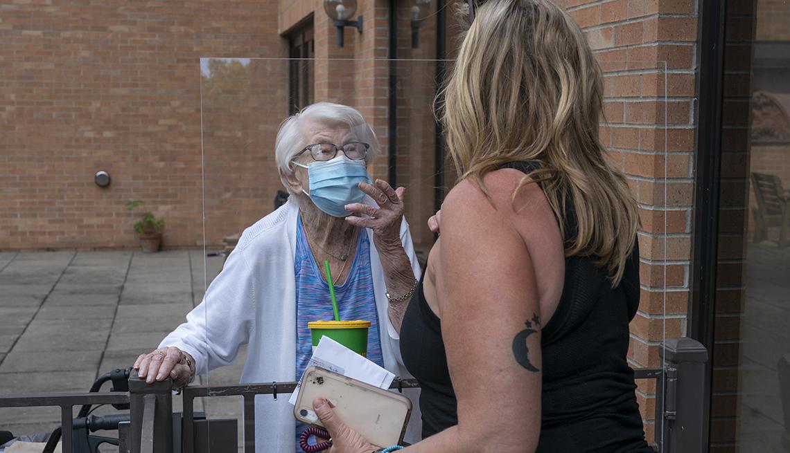 Una mujer mayor habla con otra más joven con una barrera protectora en medio