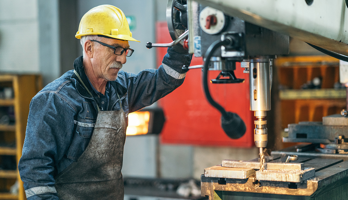 An older worker is standing by a machine