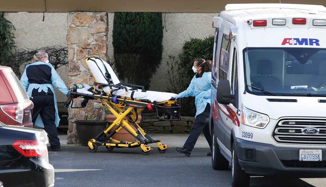 Dos funcionarios de salud empujan una camilla junto a una ambulancia