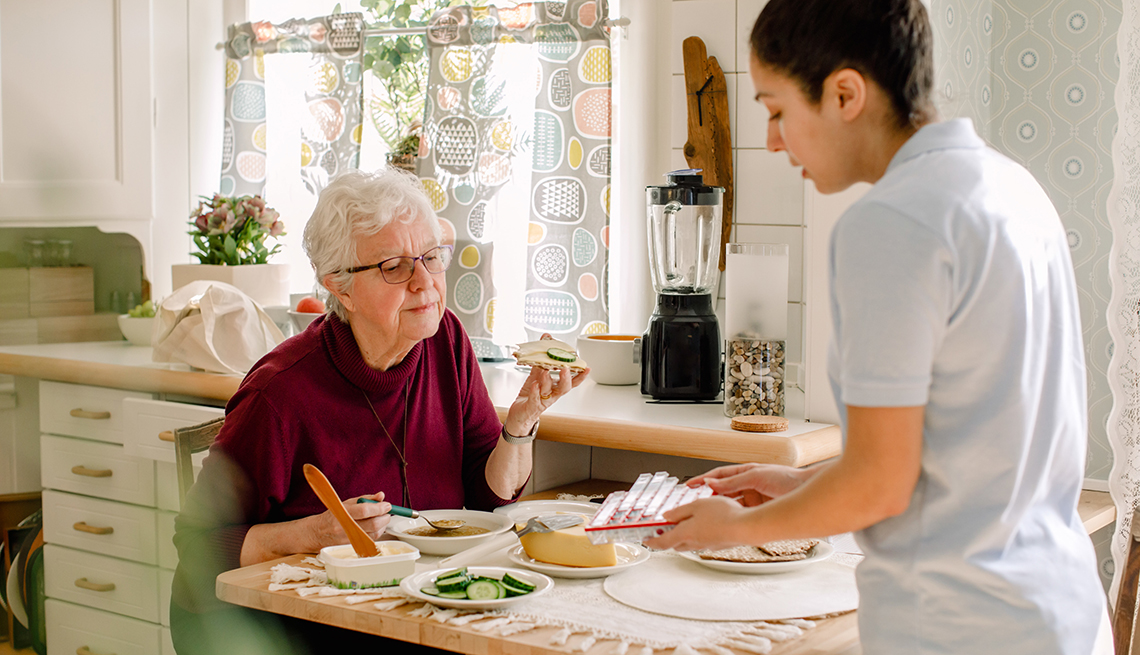 An in home care worker showing medications to a woman as she eats at her kitchen table