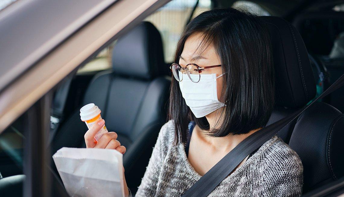 Una mujer con una máscara dentro de su auto mira un frasco de pastillas