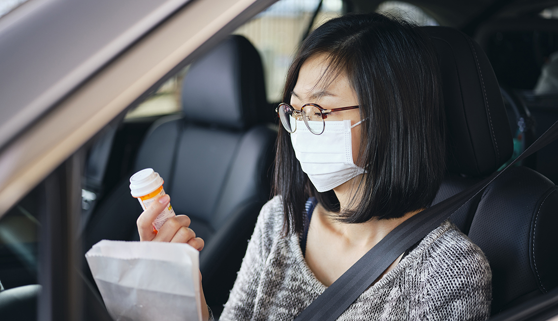 A woman wearing a mask sits in a car looking at a bottle of pills