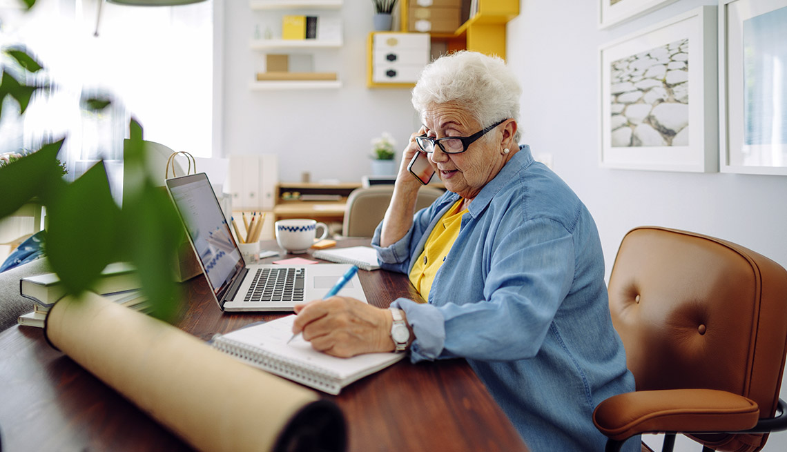 older female worker at home desk with mobile phone, laptop and notepad