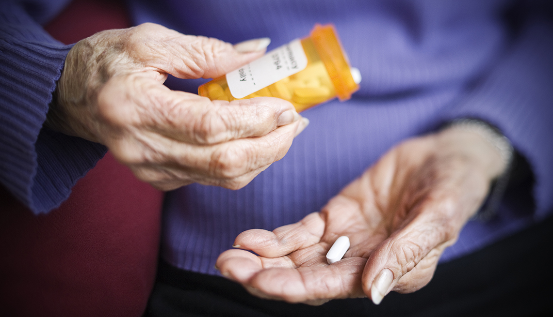 a woman is putting a pill in her hand