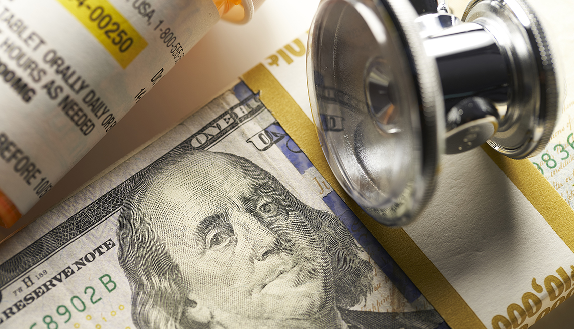 Frasco de medicamentos junto a un estetoscopio y un fajo de billetes
