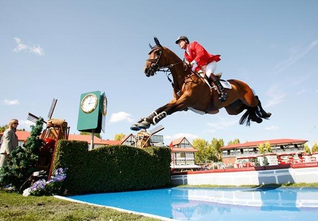 El deportista de equestre Ian Millar de Canadá salta sobre el agua con su caballo.