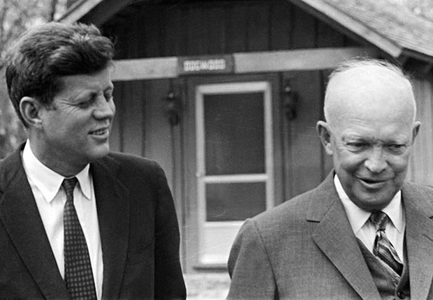 President John F. Kennedy and former President Dwight Eisenhower shown in conversation as they tour the grounds of Camp David following their meeting.