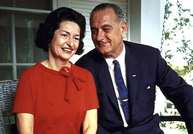 President Lyndon Johnson (R) sitting on proch swing w. wife Ladybird on morning following his landslide election win.