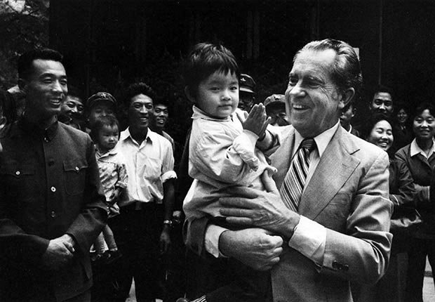Richard Nixon plays with a small child during a visit to China