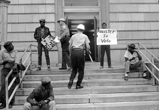 Estudiantes y trabajadores con carteles invitan a los negros a registrarse para poder votar en la antígua oficina de correos de Selma, Alabama en 1962. Estos manifestantes están a punto de ser detenidos por la policía local.