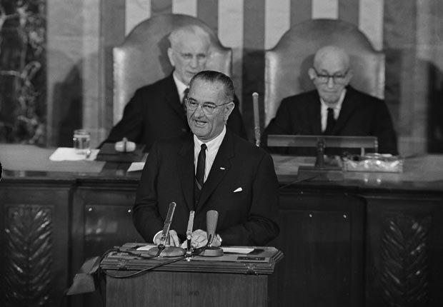 El presidente Lyndon B. Johnson habló ante una sesión del Congreso el 27 de noviembre de 1963 en busca de ayuda con los derechos civiles y la búsqueda de la paz. Detrás de él esta el Representante a la Cámara, John McCormack, a la izquierda, y el senador Carl Hayden a la derecha.