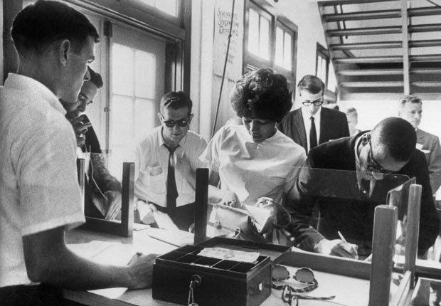 Vivian Malone y James Hood, dos estudiantes negros, se regístran en la Universidad de Alabama, 12 de junio de 1963, en Tuscaloosa. En junio de 1963, un tribunal federal prohibió cualquier interferencia del gobierno estatal con la inscripción de los estudiantes negros en la Universidad de Alabama. A pesar de esta orden, el gobernador George Wallace se nombró a sí mismo como el registrador de la Universidad y se paró en  la administración del edificio para evitar que los estudiantes se registraran. En respuesta, el presidente Kennedy federalizado la Guardia Nacional de Alabama. Un centenar de guardias escoltaron a los estudiantes a la escuela y su comandante, el general Henry Graham, ordenó a George Wallace a