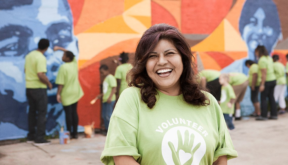 A woman smiles while a group of community volunteers paint a wall behind her.