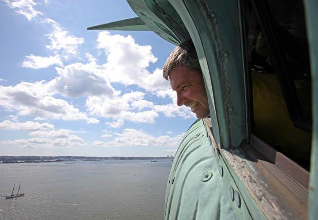 Frederick Sciulli, de 54 años, de Norfolk, Virginia le grita a la multitud abajo mientras asoma la cabeza por la ventana de la corona de la Estatua de la Libertad el 4 de julio -  4 de julio