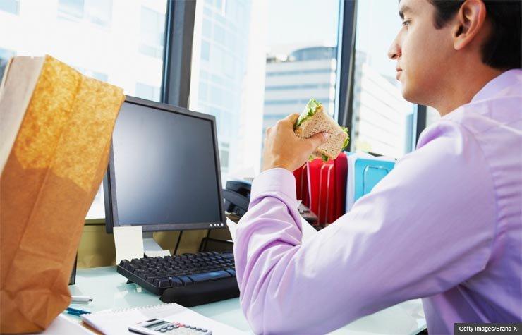 El hombre comiendose un sanduche en su oficina