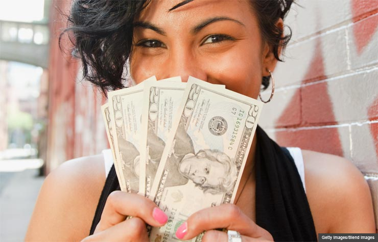 Mixed race woman holding twenty dollar bills (Getty Images/Blend Images)