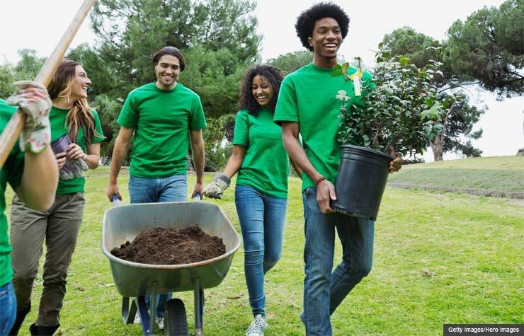Grupo de ambientalistas caminando con equipos de jardineria y una maceta en el parque