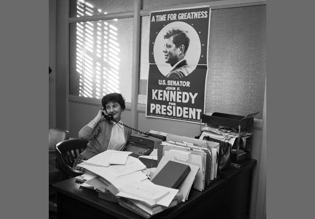 Miss Susan Stankrauff, of Miami. Florida, a staff member of Senator John F. Kennedy's looks up at a campaign poster of Senator Kennedy (D-Mass.) . After hanging it in the headquarters today.