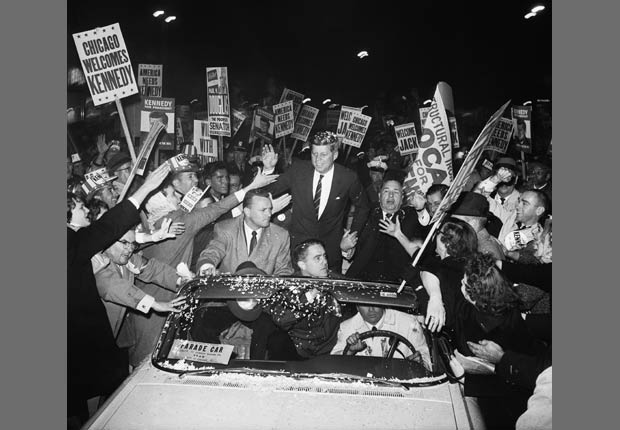 Democratic presidential candidate John F. Kennedy campaigns with Chicago mayor Richard J. Daley as a crowd of supporters swarms around his motorcade.