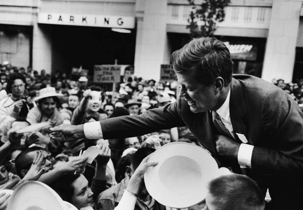 Massachusetts Senator John F. Kennedy shakes hands with a crowd in Seattle following his speech on the first day of his presidential campaign.