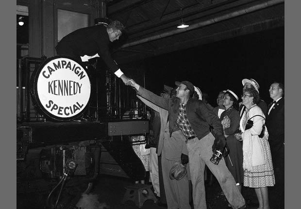 Kennedy saluda de mano de un simpatizante durante una gira relámpago de California en la campaña a la presidencia.