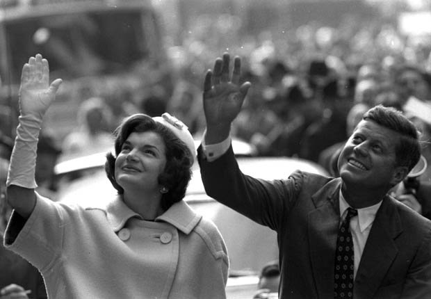 Jackie Kennedy and JFK waving to a crowd from the streets of New York City.