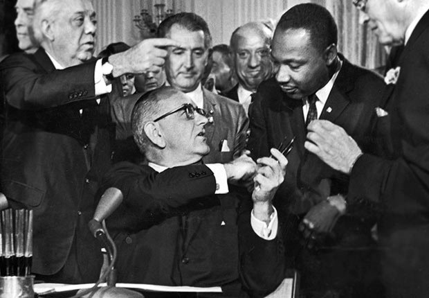 U.S. President Lyndon B. Johnson shakes the hand of Dr. Martin Luther King Jr. at the signing of the Civil Rights Act while officials look on, Washington D.C., Golden Jubilee of the 1964 Civil Rights Act