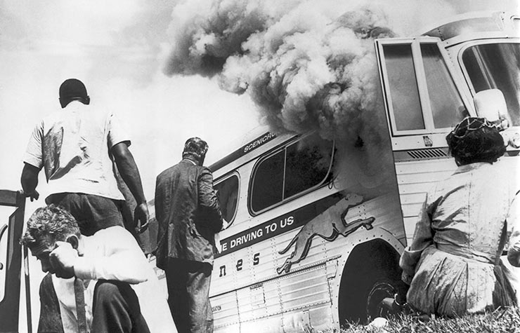 Freedom Riders on a Greyhound bus sponsored by the Congress Of Racial Equality (CORE), sit on the ground outside the bus after it was set afire by a group of whites in Anniston, Alabama, May 14, 1961, Historical Review of Leading Black Civil Rights Organizations