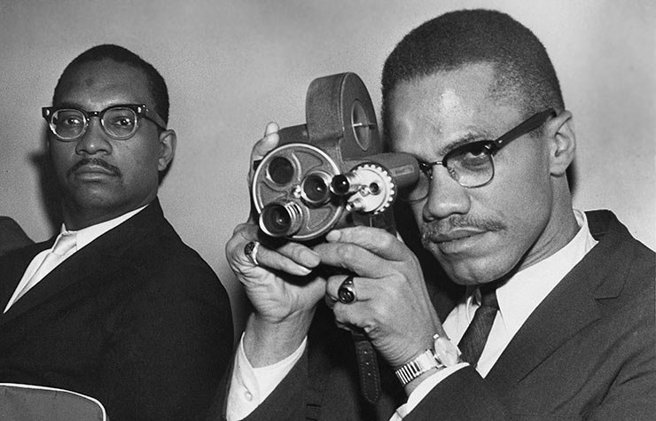African-American Muslim minister and civil rights activist Malcolm X  holding a movie camera, Historical Review of Leading Black Civil Rights Organizations