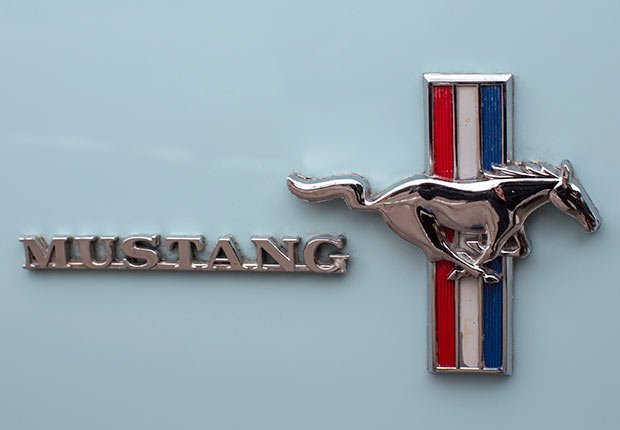 A Mustang badge is seen on the passenger side of Gail Wise's Skylight Blue 1964 1/2 Ford Mustang in Park Ridge, Illinois
