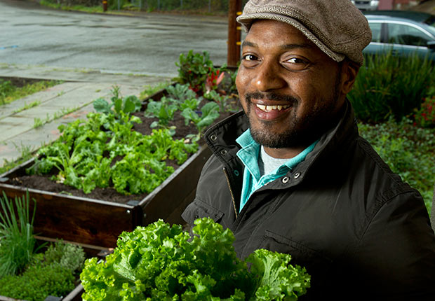 Author and chef Bryant Terry poses for a photograph with some freshly picked mustard greens from his home garden in Oakland, California.