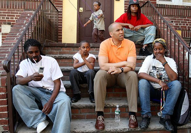 Newark mayor Cory Booker sits and listens in the courtyard of an apartment complex on Hawthorne Avenue in Newark.