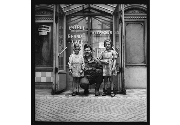 Photographer John Morris poses with two French children in Bayeux, Normandy, July 23, 1944.