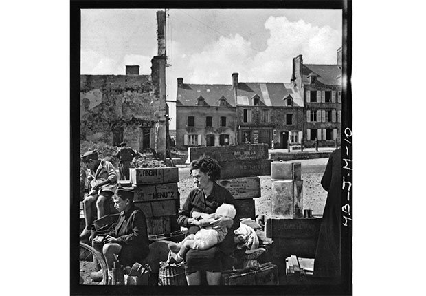 Refugees in Montebourg, Normandy. on July 24, 1944. The cases are U.S. food rations from the Raritan Arsenal in Metuchen, New Jersey.