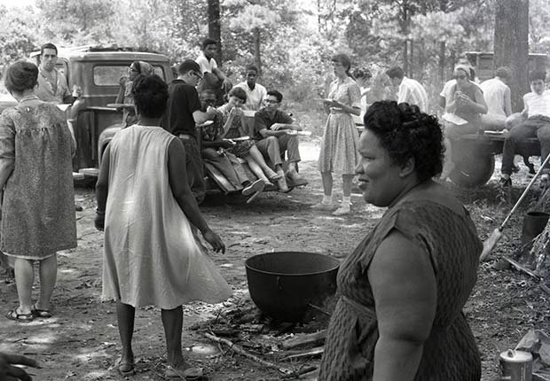 Black and white civil rights demonstrators standing and sitting and talking in woods