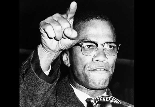 Malcom X speaking in front of a microphone with his arm raised and finger pointing