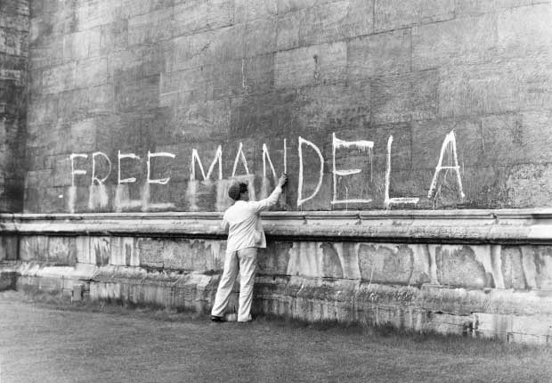 Child writing 'Free Mandela' on a wall in paint
