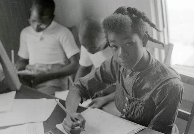 African American girl sitting at a desk and writing