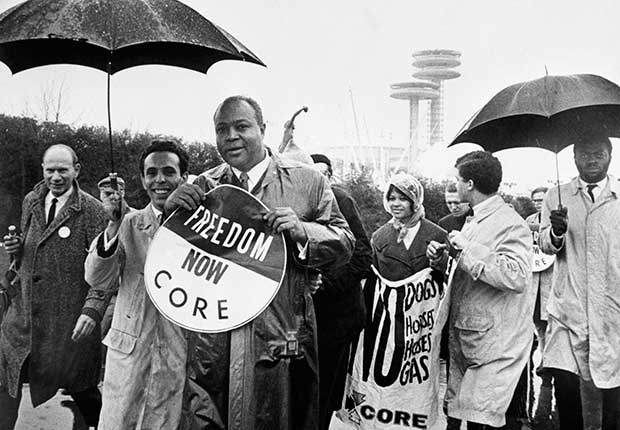 Group of people walking with umbrellas and holding signs that read Freedom Now CORE