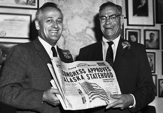 Egan and Bartlett hold edition of the Daily News-Miner of Fairbanks, with a headline announcing Alaska's statehood, and a picture of the new United States flag.